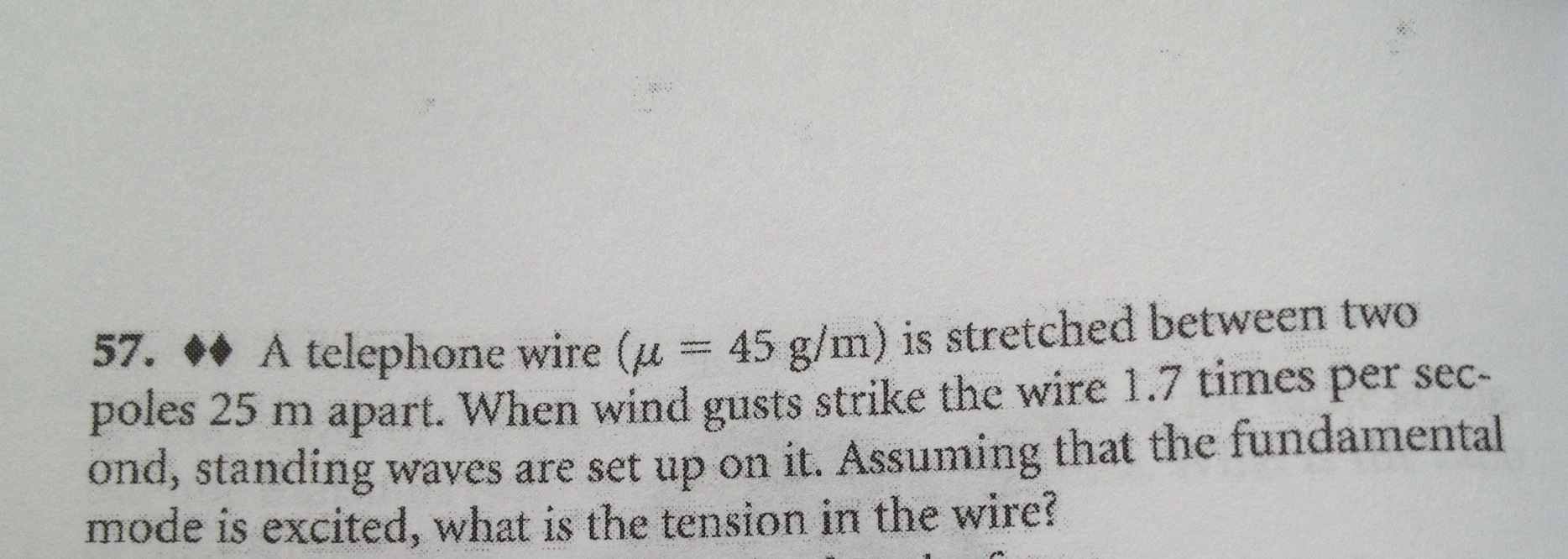 A telephone wire (mu = 45 g/m) is sretched between